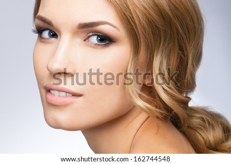 Portrait of beautiful young happy smiling woman with blond hair, over grey background - stock photo