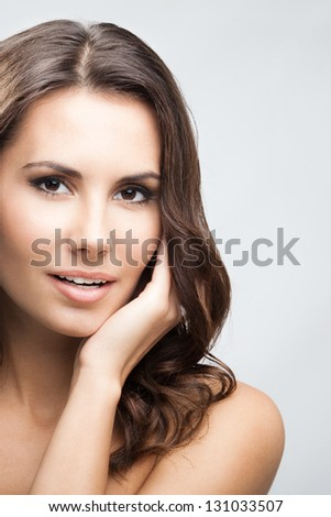 Portrait of beautiful young happy smiling woman with long curly hair, over grey background