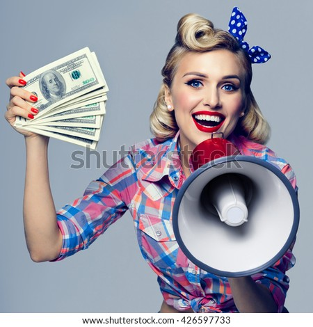 Portrait of beautiful young happy smiling woman with money and megaphone, dressed in pin-up style. Caucasian blond model posing in retro fashion and vintage concept studio shoot.
