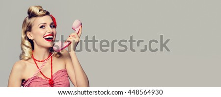 Portrait of beautiful young happy woman with phone, dressed in pin-up style. Caucasian blond model posing in retro fashion and vintage concept studio shoot. Blank copyspace area for slogan or text.