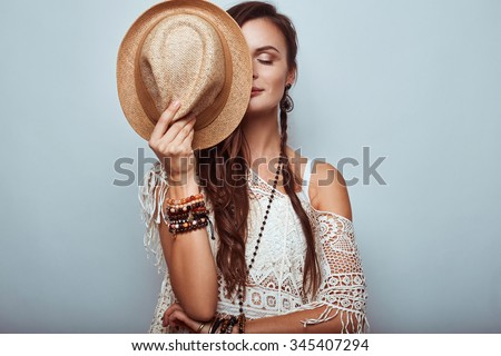 Portrait of beautiful young hippie woman wearing hat in studio - stock photo
