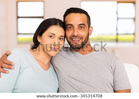portrait of beautiful young indian couple relaxing at home - stock photo