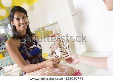 Portrait of beautiful young Indian woman paying for cushion through credit card at shop - stock photo
