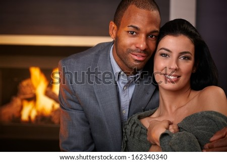 Portrait of beautiful young interracial couple, smiling at home by fireplace. - stock photo