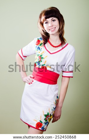 Portrait of beautiful young lady in artistic handmade embroidered dress - stock photo