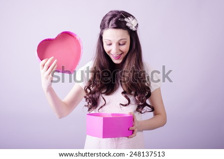 Portrait of beautiful young lady looking at love heart gift box