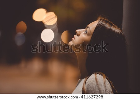 Portrait of beautiful young lady looking up, city street in the night, evening lights bokeh outdoors background  - stock photo