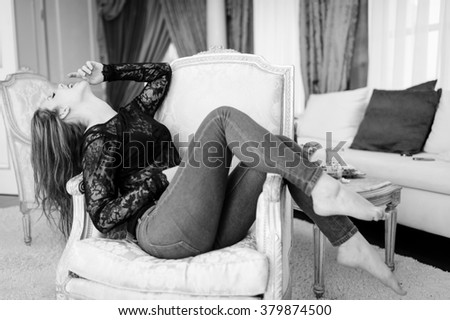Portrait of beautiful young lady relaxing in chair on luxury interior background - stock photo