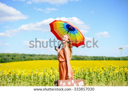 Portrait of beautiful young lady with rainbow umbrella and retro suitcase beside sunflowers field. Pretty girl laughing on sunny countryside background.