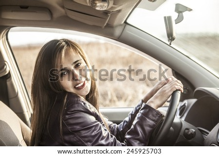 Portrait of beautiful young latin hispanic woman in the new car - indoor talking to an imaginary police, companion, companion, who asks for directions or the right to drive and Documents
