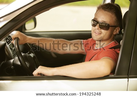 Portrait of beautiful young man in car smiles.
