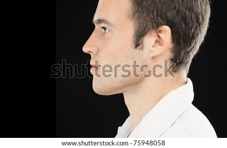 Portrait of beautiful young man in white suit in profile, on black background.