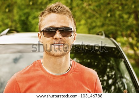 Portrait of beautiful young man smiling about car.
