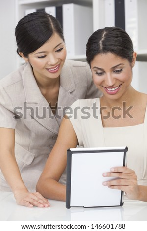 Portrait of beautiful young mixed race Hispanic woman or businesswoman in office meeting with Chinese Asian female colleague using a tablet computer