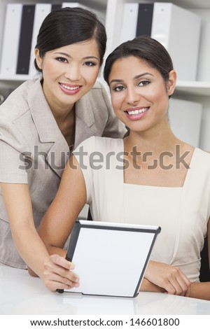 Portrait of beautiful young mixed race Hispanic woman or businesswoman in office meeting with Chinese Asian female colleague using a tablet computer  - stock photo