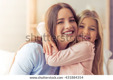 Portrait of beautiful young mother and her daughter hugging, looking at camera and smiling - stock photo