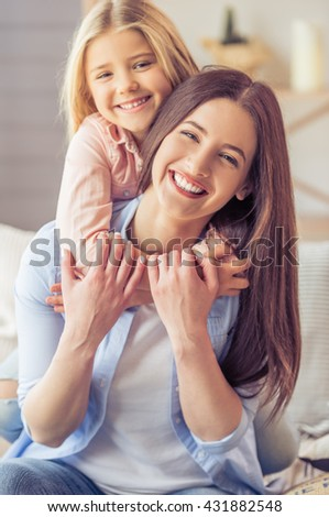 Portrait of beautiful young mother and her daughter hugging, looking at camera and smiling while sitting on sofa at home - stock photo