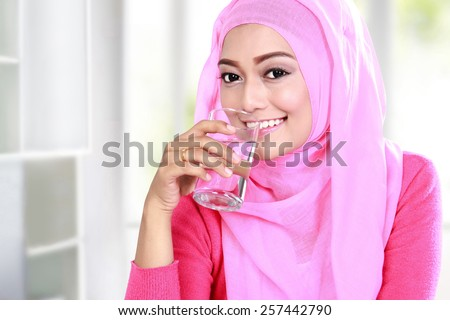 portrait of beautiful young muslim woman drink a glass of water - stock photo