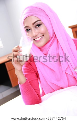 portrait of beautiful young muslim woman drinking a glass of milk for breakfast - stock photo
