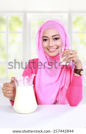 portrait of beautiful young muslim woman have a breakfast with milk - stock photo