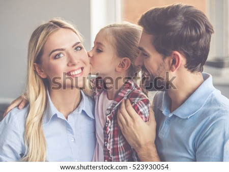 Portrait of beautiful young parents and their cute little daughter hugging, looking at camera and smiling. Girl is kissing her mom