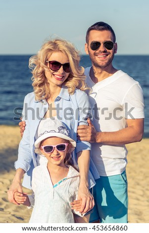 Portrait of beautiful young parents and their cute little daughter in casual clothes and sun glasses looking at camera and smiling, sunny beach in the background - stock photo