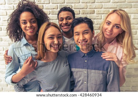 Portrait of beautiful young people of different nationalities looking at camera and smiling, against white brick wall - stock photo