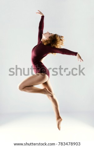 Portrait of beautiful young professional dancer dancing over white background.