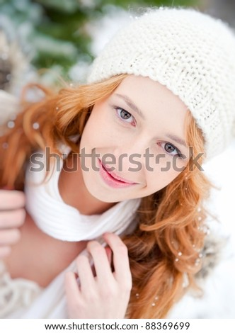 Portrait of beautiful young red hair woman outdoors in winter looking at camera and enjoying snow