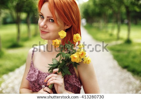 Portrait of Beautiful Young Red Hair Woman Smiling and Holding Spring Flowers. Headshot, Looking in Camera. - stock photo