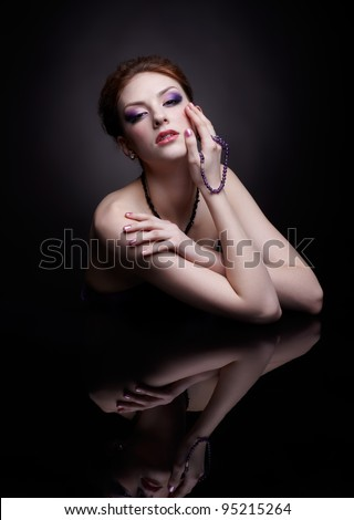portrait of beautiful young red-haired woman at dark reflecting table - stock photo