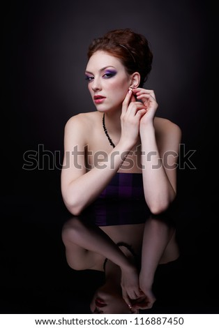 portrait of beautiful young red-haired woman sitting at dark reflecting surface - stock photo
