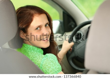 Portrait of beautiful young redhead caucasian woman in the new car - indoor - stock photo