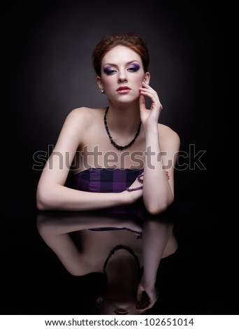 portrait of beautiful young redhead woman at dark mirror table - stock photo