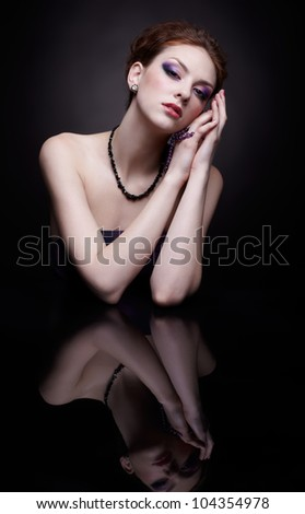 portrait of beautiful young redhead woman at dark reflecting table - stock photo