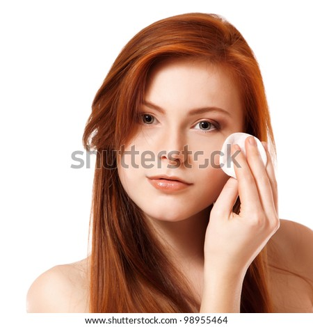 Portrait of beautiful young redheaded woman delete cosmetics with makeup sponge. Isolated on white background