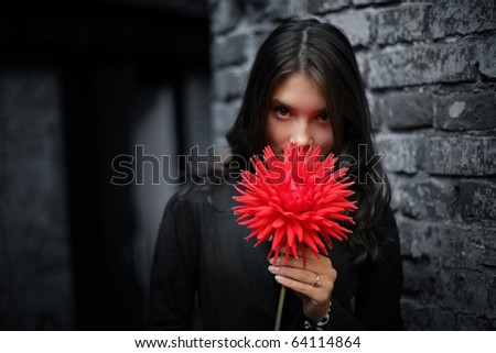 Portrait of beautiful young romantic Asian woman with red dahlia flower