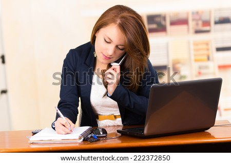 portrait of beautiful young secretary working from desk talking on cell phone - stock photo