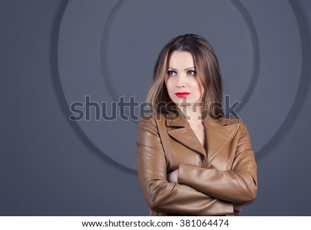 portrait of  beautiful young self-confident woman in brown leather jacket standing with her hands crossed - stock photo