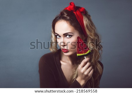 Portrait of beautiful young sexy blonde with a red armband with red lips with a lollipop with watermelon shape sensual temptation to make up pin up - stock photo