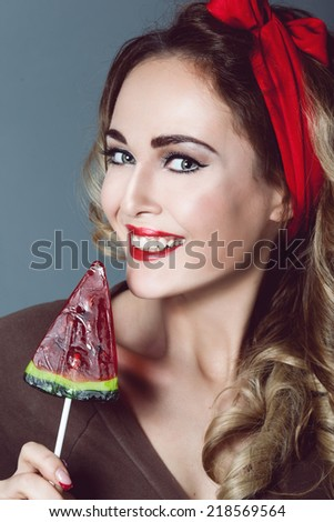 Portrait of beautiful young sexy blonde with a red armband with red lips with lollipop form of watermelon with a smile, happy teeth sensual temptation to make up pin up - stock photo