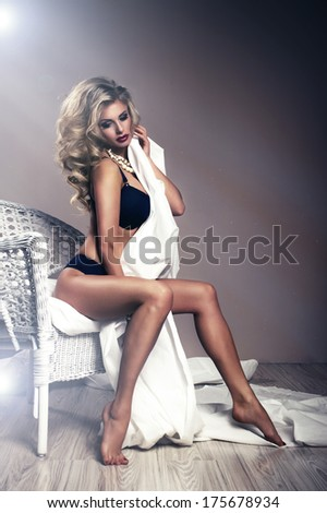 Portrait of beautiful young sexy woman sitting on chair - stock photo