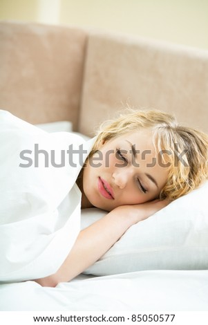 Portrait of beautiful young sleeping woman at bedroom