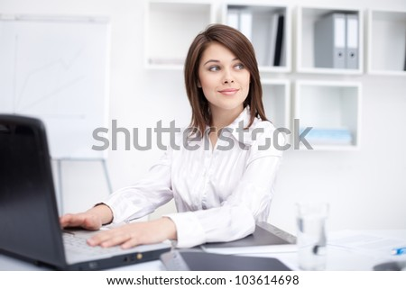 Portrait of beautiful young smiling business woman working on a laptop at office - stock photo