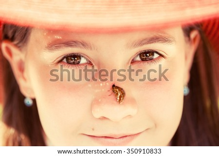 Portrait of beautiful young smiling girl with butterfly on nose in summer hat looking into camera. Summertime outdoors horizontal closeup image.