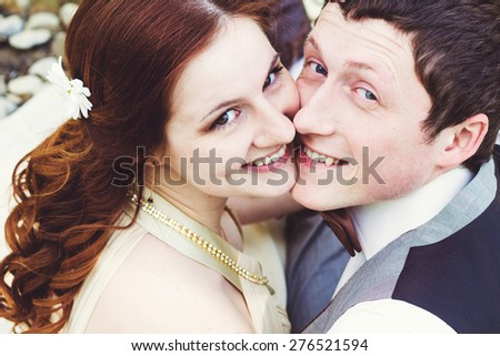 Portrait of beautiful young smiling groom and wife. - stock photo