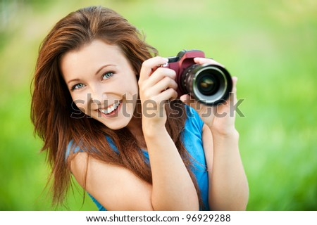 Portrait of beautiful young smiling woman with camera at summer green park - stock photo