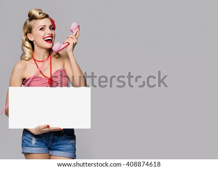 Portrait of beautiful young smiling woman with phone and blank signboard, dressed in pin-up style. Caucasian blond model posing in retro fashion and vintage concept studio shoot, on grey background. - stock photo