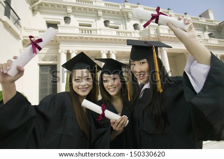 Portrait of beautiful young students with diplomas standing in front of university - stock photo