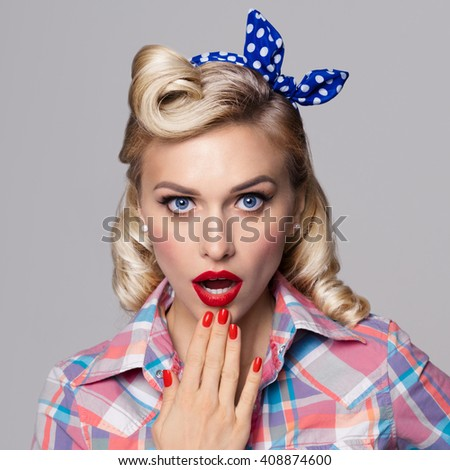 Portrait of beautiful young surprised woman, dressed in pin-up style. Caucasian blond model posing in retro fashion and vintage concept studio shoot, on grey background. - stock photo